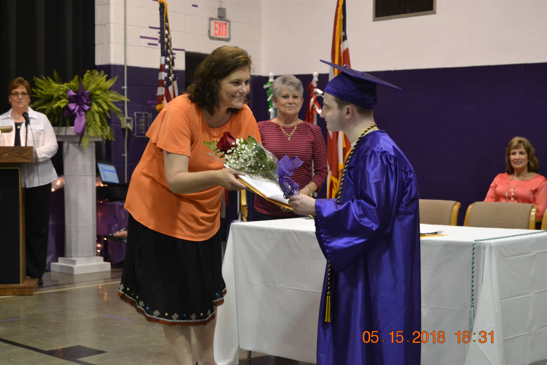 Superintendent handing diploma to student