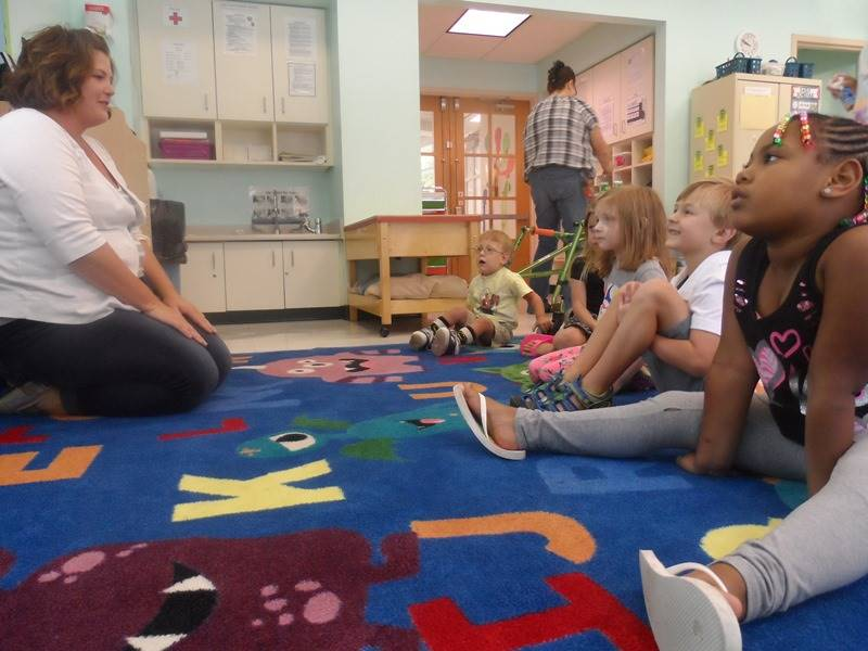 Students sit in front of a teacher